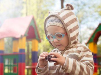 Ребенок в очках на детской площадке рассматривает игрушку