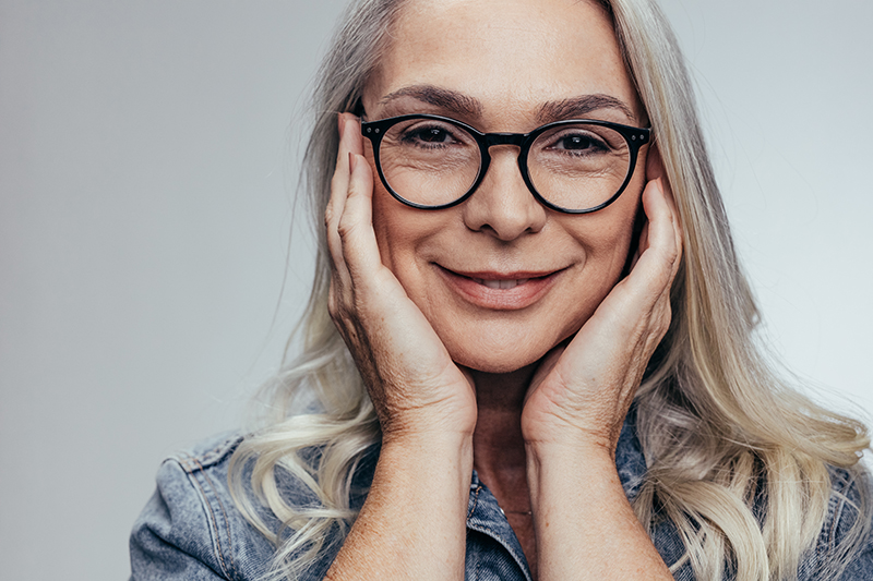 Senior woman with hands on her face against grey background. Positive mature woman in casual denim shirt.